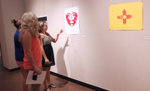 """Sarah Adams, a junior in  kinesioloy, Collin Darland, a senior in art education, and Kelby Doughty, a senior in sports management look at the posters during the opening. """"The art is very interesting, I enjoy the way he uses print making in the music field,"""" Darland said."""