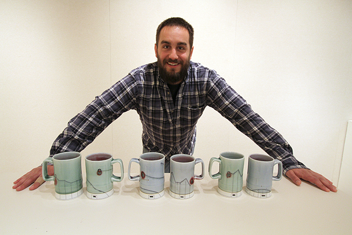 "Mike Kern, resident artist, stands behind a row of mugs he created. Kern said,""I make functional pottery so people can use it. When I'm making something the thought is always in the back of your mind. Like, will it pour properly."""