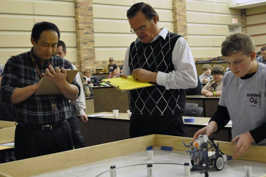 Sheldon Wang, professor and chair of the McCoy School of Engineering, and Richard P. Simpson, an assistant professor in computer science, judge Dayde Whitworth's robot for the TCEA Area 9 Robotics Competition at the Dillard College of Business on Jan. 25.