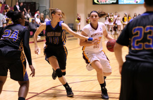 Kirsti Degelia, senior in math, dribbles past an Angelo State defender during the senior night, white out game.