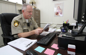 Sergeant Kelly Maloney sits in his office and goes over paperwork he received in the internet hoax case Thursday morning. Photo by Lauren Roberts