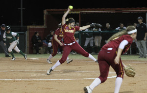 Katlyn Holmes, freshman in nursing, pitches with a runner on first during the Holiday Inn/MSU Invitational. MSU defeated Northeastern State 8-5 Feb. 15 at Mustang Park. Photo by Lauren Roberts
