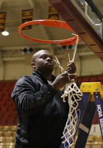 Nelson Haggerty, head men's baketball coach, pulls down the net during the men's basketball team net cutting ceremony Monday night in D.L. Ligon Coliseum after winning the Lone Star Conference Championship. Photo by Lauren Roberts