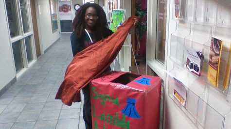 President of Sigma Lambda Alpha sorority Natalie Nduku stands beside a donation box outside of the student development office holding a dress that was donated for neglected and abused children.  Photo by Mandi Elrod