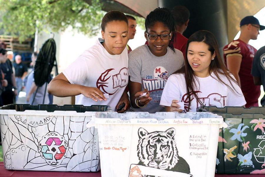 Nicole Smallwood, sophomore in sports and leisure studies, Shatoia Gober, junior in sports and leisure studies, and Tam Vuong, junior in marketing, decide which bin they are going to vote for at the Earth Day fair.