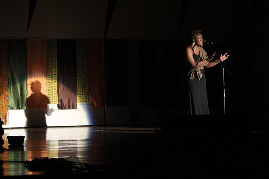 Danielle Thomas, senior in finance, opens the night with a poem in Akin Auditorium Saturday night at the Caribbean Students Organization: Expressions. Photo by Lauren Roberts