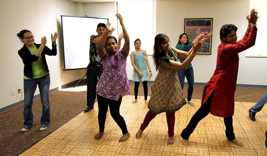 Luzmila Moreno, triple major in criminal justice, political science and spanish, joins members of the Midwestern Indian Students Association for a group dance at the International Fair music breakout session on March 29. Photo by Ethan Metcalf.