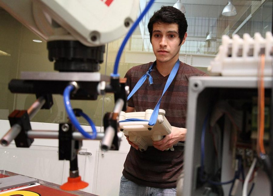 Alejandro Hernandez, senior in mechanical engineering, works on his senior design project using a hydraulic peck-drill in the McCoy training lab Tuesday afternoon. Photo by Eddie Miller