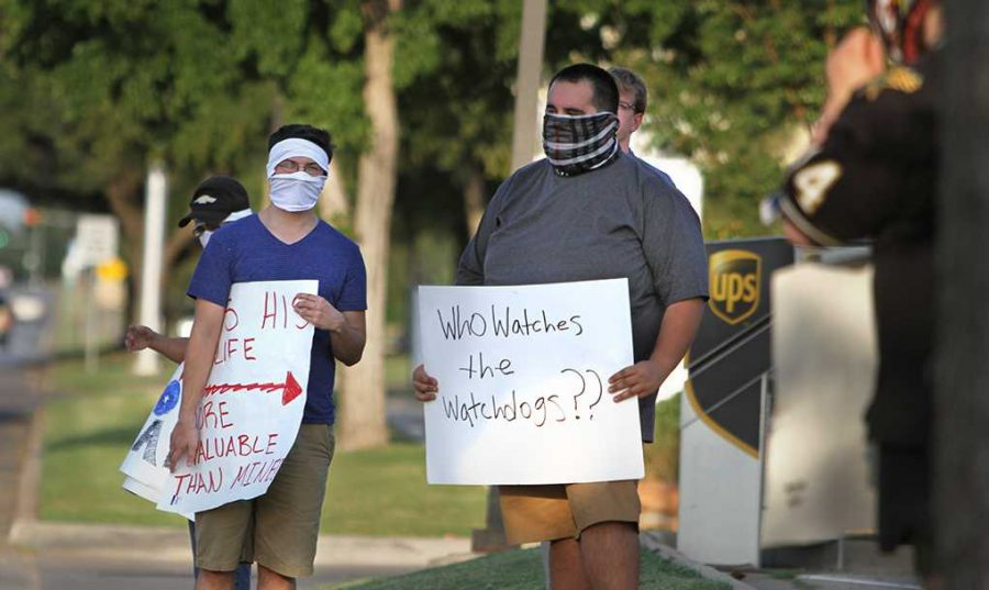 English sophomore Stephen Wright and an unidentified man stand on Midwestern Parkway. Wright holds a sign reading,