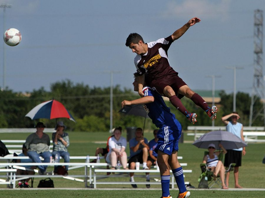 Juan Farres, economics junior, heads the ball over a FC Dallas defender at Moneygram Soccer Park in Dallas Saturday afternoon. The match ended 2-0. Photo by Lauren Roberts