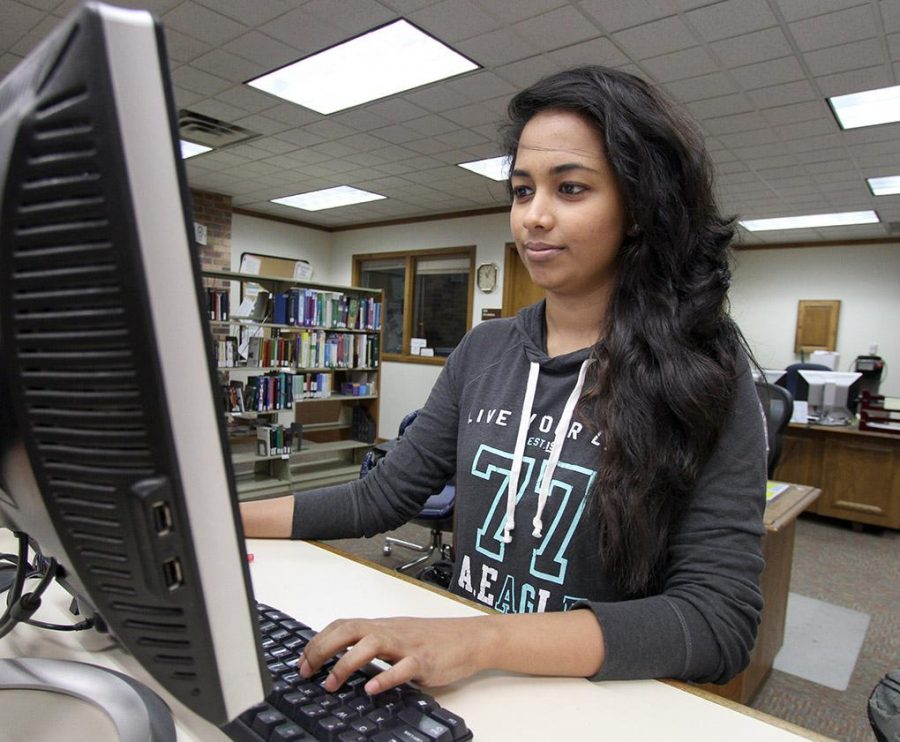 Nadeeha Mohotti, accounting senior, looks up book information at the front desk in Moffett Library Tuesday. Mohotti started working in the libary last summer. I like to be here and work here. The staff are friendly, Mohotti said. Photo by Lauren Roberts