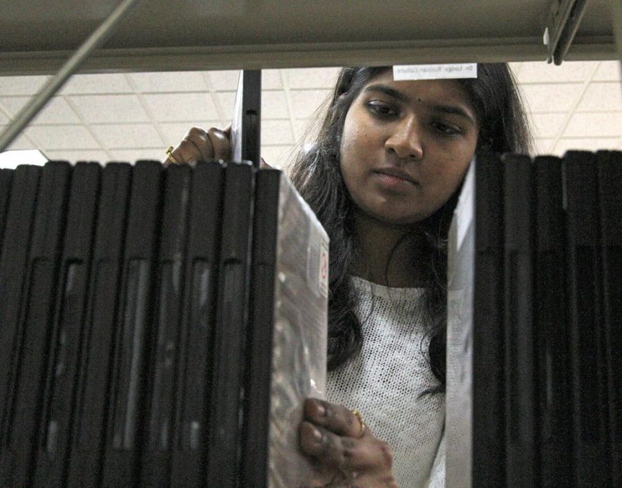Pragna Vemuri, computer science graduate student, returns materials to the shelfs behind the front desk in Moffett Library Tuesday. Vemuri just started working in the libaray this semester.