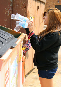 Alexis Martinez, biology freshman, poses for a photo putting her water bottles in the recycling bin behind the dorm halls.  Photo illustration by Rachel Johnson | The Wichitan