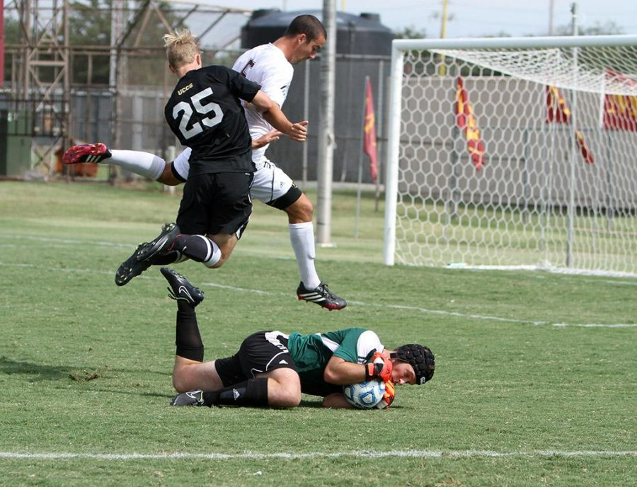 MSUs Kalen Ryden, mass communication senior, and Colorado-Colorado Springs freshman Jake McAllister jump over MSUs goal keeper Nick Petolick, business management junior, as Petolick holds on to the ball. Photo by Lauren Roberts