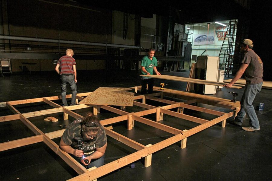Crystal Carter, theater junior, Leonard Loughner, theater sophomore, and Maxwell Norris, theater senior, place a board onto the platform that is being built on the Fain Theater stage Friday afternoon. Friday was the first day for set constuction of August: Osage County, the theater departments first production of the school year. Photo by Lauren Roberts