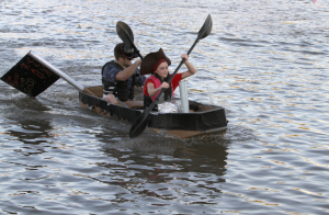 William Winkler, radiology junior, and Sarah Guthrie, radiology senior, race to the shore in the Radiology club boat at the carboard boat race in Sikes Lake on Oct. 24. Photo by Lauren Roberts