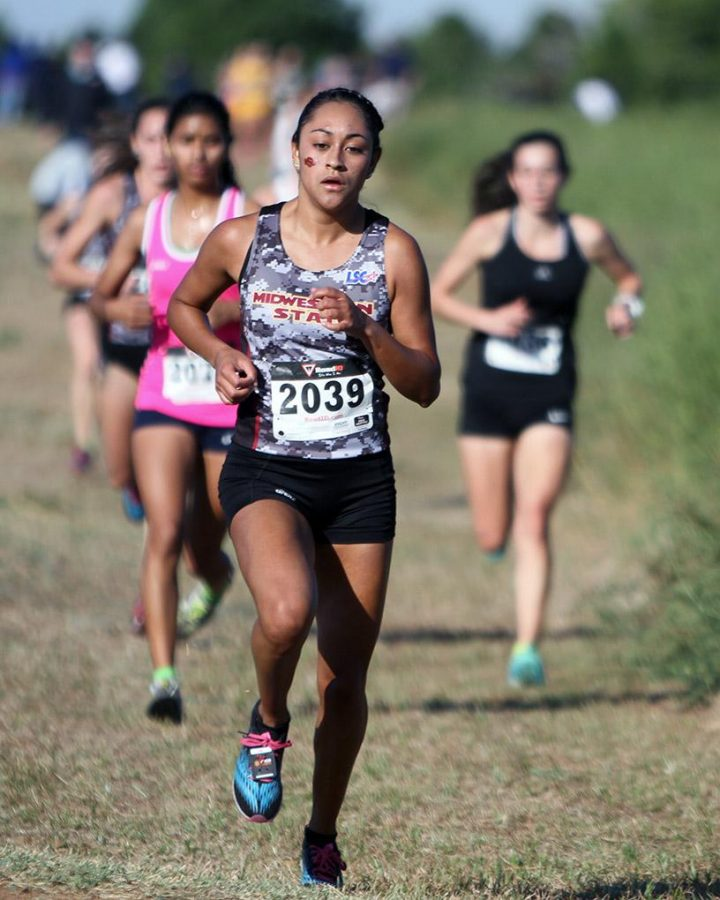 Ana Lopez, exercise physiology and Spanish junior, runs in the Cross Country Carnival Saturday at the former Hawk Ridge Golf Course. Lopez finished in twelfth place with a personal-best of 23:30.90. Photo by Lauren Roberts