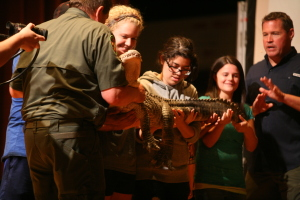 Jeff Corwin interacts with members of the audience, Madison Brechbulh, nursing freshman, Amy Calderon, freshman in athletic training, and other students on stage as he talks about an alligator during his visit to Midwestern State University, Artist Lecture Series, Oct. 2, 2014. Photo by Sam Croft