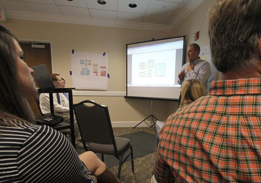 Joe Stramberg, principal project manager of Treanor Architects, goes over the mass communication plans in the Kiowa Suites Tuesday. Photo by Lauren Roberts