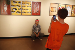 Cara Mack, math senior, takes a photo of Lucia Trejo, exercise physiology senior, in front of photgraphs taken by Gary Goldberg at the Faculty Art Exhibit on Oct. 31. Photo by Ethan Metcalf.