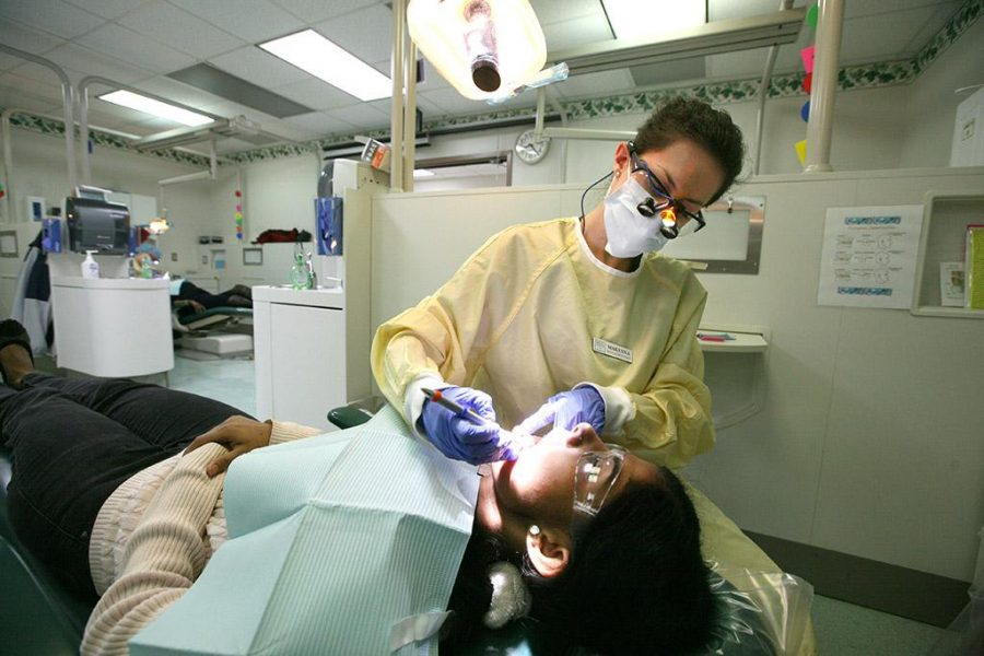 Makenna Smith, dental hygiene senior, begins examing Swati Gurbhele, biology graduate student Gurbhele said she heard about the dental clinic in an email and wanted to get a cleaning before she graduates in December. Photo by Ethan Metcalf.