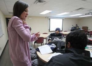 Sultan Alanizi and Riyadh Al Saho ask Brittany Norman, English teaching assistant, for help with English workbooks in the Intensive English Language Institute conversation and grammar class Tuesday. Photo by Lauren Roberts