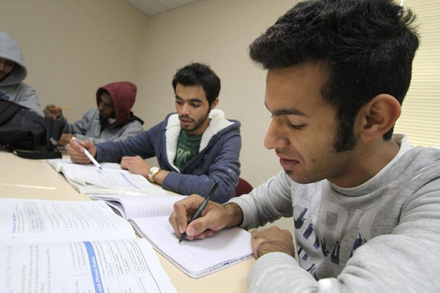 Saleh Alhariqi and Nawaf Almutairi go through English workbooks in the Intensive English Language Institute conversation and grammar class Tuesday. Photo by Lauren Roberts