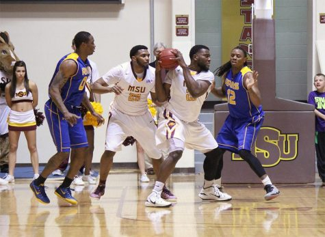 Abiodun Adegoke, senior, gets the rebound while his teammate, Khapri Alston, junior, holds back a Angelo State player during the game on January 21 in the D.L. Ligon Coliseum, where Angelo State won 72-55. Photo by Rachel Johnson