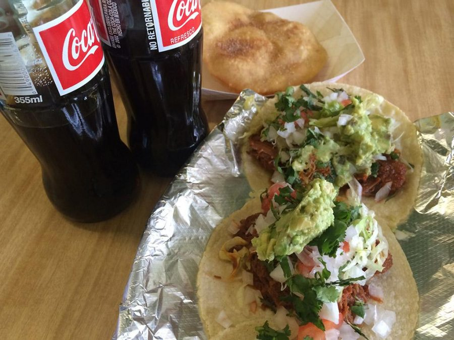 Pork street tacos with red chile sauce, guacamole, tomatoes, onions and cilantro. Mexican-bottled Coke and sopapillas.