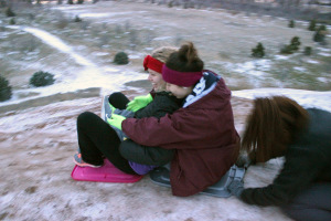 Alexis Carrizales, biology freshman, pushes Norma Nieto, sophomore business, and Madison Brechbuhl, nursing freshman, down 'The Hill' on makeshift sleds during the first snow day, Monday February 23. Photo by Rachel Johnson