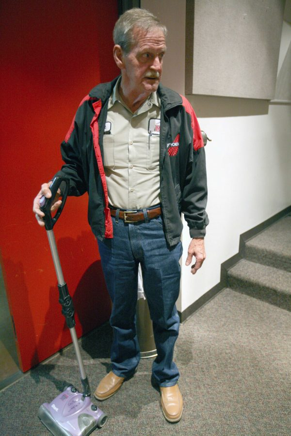 Robert Entrekin, custodian, talks with a news reporter while he vacuums a lecture room in the C wing of the Fain Fine Arts building, Monday, April 27, 2015.