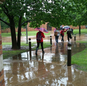 Students avoid deep puddles walking from Prothro-Yeager to Clark Student Center as the rain continues to pour down on campus April 27. Photo by Francisco Martinez