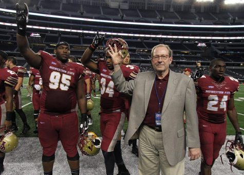 University President Jesse Rogers holds up the Indian sign with the football players as they hold up the Mustang during the playing of the school song after the Midwestern State University v. Eastern New Mexico game at AT&T Stadium in Arlington, Sept. 20, 2014. Photo by Lauren Roberts