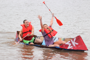 Shane Jones, undecided  sophomore, and Destiny Zynda, exercise physiology junior, are the first to finish at the MSU Cardboard Boat Race where students and organizations build a boat out of cardboard, and duck tape and race across Sikes Lake, Oct, 30. Photo by Francisco Martinez