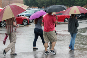 A group of people, near Fain Fine Arts, visiting campus are given a tour even though its pouring rain, and parts of campus are flooded. Photo by Francisco Martinez.