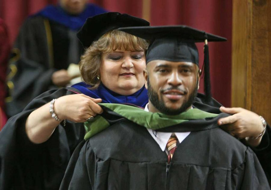 Deborah Garrison, associate vice president for academic affairs and dean of the graduate school, presents hoods to the recipients of master's degrees at Midwestern State University graduation, Wichita Falls Multi-Purpose Event Center, Dec. 14, 2013. Photo by Ethan Metcalf.