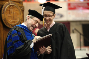 Retiring university President Jesse Rogers signs a copy of Sunwatcher magazine for Wichitan Editor Ethan Metcalf at Midwestern State University graduation, May 16, 2015 at the Kay Yeager Coliseum. Photo by Francisco Martinez