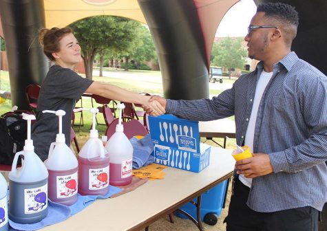 Ashley Burkhart, intern at the Baptist Student Ministry, introduces herself to Tyre Browning, nursing freshman, at the free snowcone stand provided by the BSM on Move-In Day August 18, 2015. Photo by Rachel Johnson