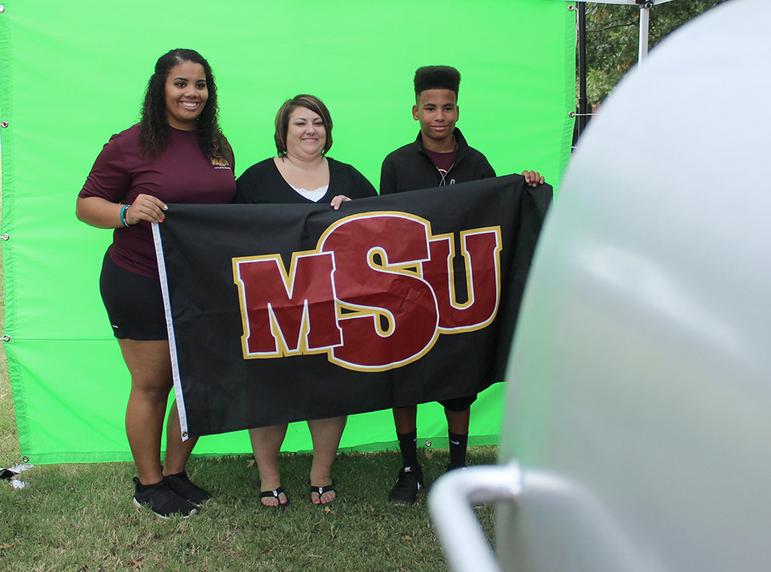 Sierra Jones, athletic training senior, Shana Hancock, mother of Sierra, and Devin Hancock, Sierra's brother, get their picture taken at one of the booths in the Quad put up for Family Day, Sept. 26. Photo by Rachel Johnson