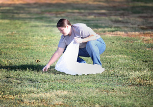 Sarah Cobb, mathematics assisstant professor, picks up trash in the grass as a volunteer at the Sikes Lake cleanup, Sept. 12, 2015. Photo by Rawlecia Rogers.