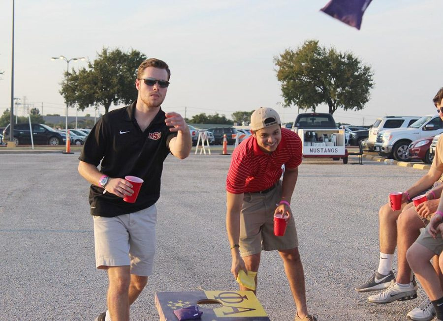 Austin Leverage, finance junior, tosses the ball while his partner, Jared Rivas, biology sophomore, during a game of bean bag toss set up by Sigma Alpha Epsilon in the new designated tailgating section of the parking lot outside of Memorial Stadium, Saturday Sept. 5, 2015. Midwestern State beat Truman State 31-3 in their opening game of the season. Photo by Rachel Johnson