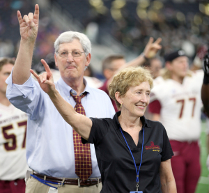 """Charlie Carr, athlectic director, and Suzanne Shipley, Midwestern State University president, throw up the """"stang sign"""" while the band performs the alma mater during the end of Eastern New Mexico University vs. MSU game at AT&T Stadium, Sept. 19. Photo by Francisco Martinez"""