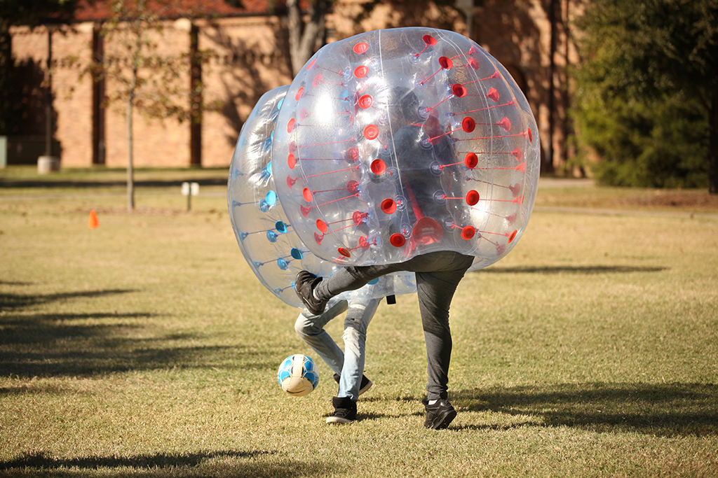 Salman Shuqairy, Intensive English Language Institute program freshman, kicks the ball across to Khalid Qadiri, IELI sophomore, during a game of Bubble Soccer that the University Programming Board put on in the Quad near the Bolin Fountain Oct, 27. Photo by Francisco Martinez
