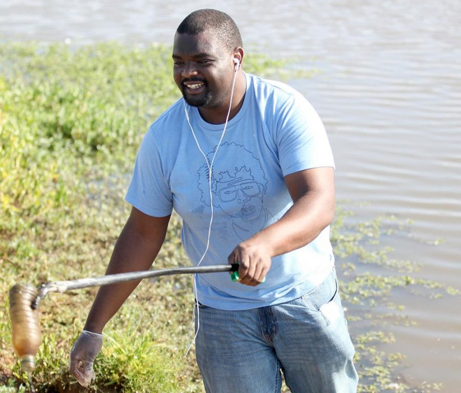 Damian De Silva, economics senior, volunteers at the Sikes Lake cleanup on Sept. 12. Photo by Rawlecia Rogers.