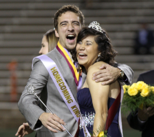 Sabina Marroquin, history education senior, won 2014 Homecoming Queen and Elijah wire, sport and leisure studies senior, hug with excitement when they find out the won 2014 Homecoming Queen and King, Saturday night at Memorial Stadium. Photo by Rachel Johnson