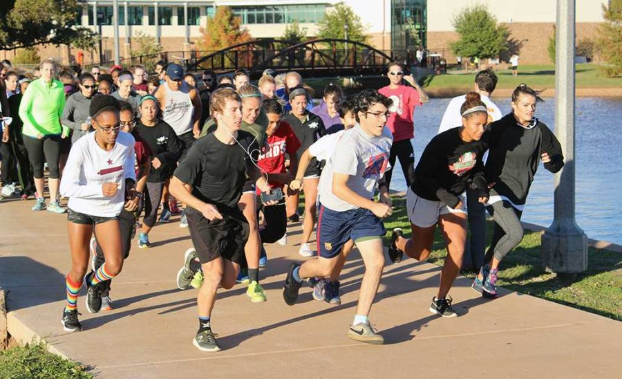 Caleb Hannon, assistant director of rec sports and Wellness center, sounds off for participants to begin running in the Turkey Trot 5K around Sikes Lake Nov. 17. The entry fee was one canned food item. Winners won a frozen turkey. Photo by Francisco Martinez