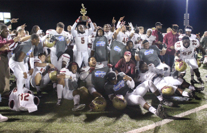 The football players celebrate their victory in the Lone Star Conference Championship game against Texas A&M-Commerce, by posing for a group photo while Brandon Gordon, education senior, holds up the trophy, Nov. 14.