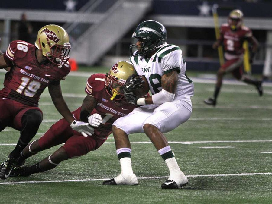 Eastern New Mexico running back Jordan Wells is tackled by Marqui Christian, criminal justice junior, at the  Midwestern State University v. Eastern New Mexico game at AT&T Cowboys Stadium in Arlington, Sept. 20, 2014. File photo by Lauren Roberts