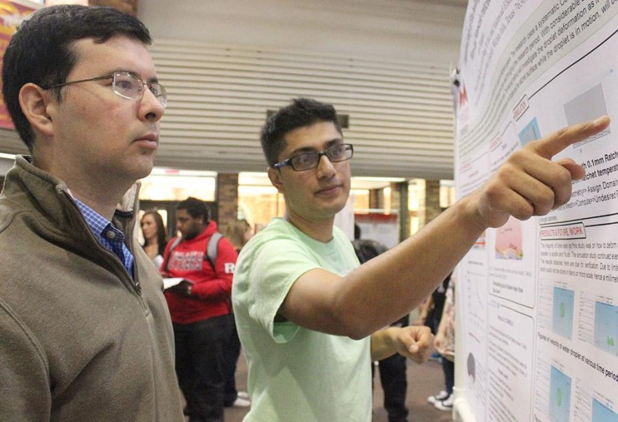 Kiran Chapagain, mechanical engineer junior, presents his poster on Computational Study of Film Boiling Droplet Motion on Micro- and Nanoscale Ratchets to Eduardo Colmenares, professor of computer science and one of the judges, at the Undergraduate Research and Creative Activity Forum, held in the CSC Atrium, Nov. 19. Photo by Rachel Johnson