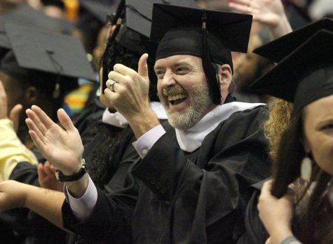 Andrew Herbert, clinical mental health, applauds his family members in the audience during the part in the ceremony where they have the graduates recognize their friends, family, professors, and people who helped them get to graduation day in Kay Yeager, Dec. 12.